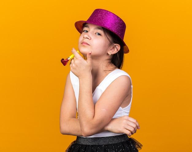 Jovem caucasiana confiante com chapéu de festa roxo segurando o apito isolado na parede laranja com espaço de cópia