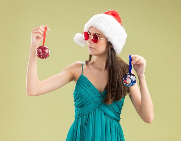 Jovem caucasiana confiante em óculos de sol com chapéu de papai noel segurando e olhando para enfeites de bola de vidro