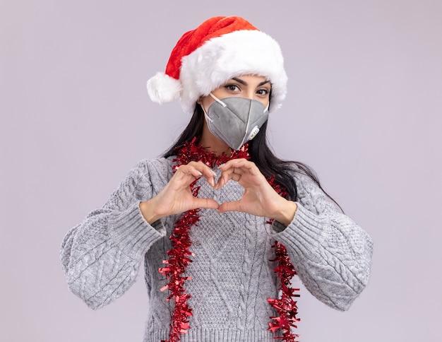 Jovem caucasiana confiante usando chapéu de natal e guirlanda de ouropel em volta do pescoço com máscara protetora, olhando para a câmera, fazendo um sinal de coração isolado no fundo branco