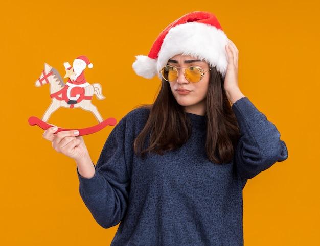 Jovem caucasiana confusa de óculos de sol com chapéu de papai noel coloca a mão na cabeça, segurando e olhando para o papai noel na decoração de cavalo de balanço isolada na parede laranja com espaço de cópia