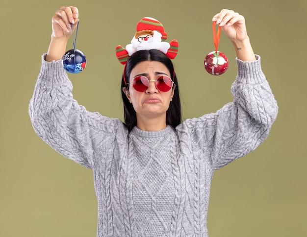 Jovem caucasiana confusa usando bandana de papai noel com óculos levantando enfeites de natal olhando para a câmera isolada em fundo verde oliva