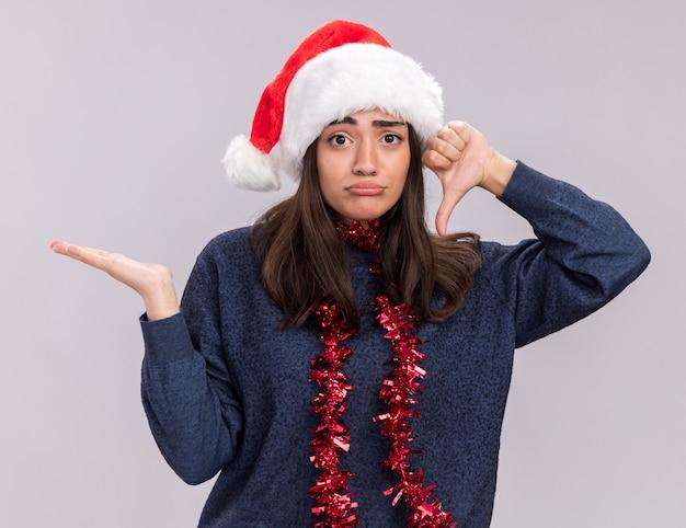Jovem caucasiana desapontada com chapéu de papai noel e guirlanda em volta do pescoço mantém a mão aberta e polegares para baixo, isolado na parede branca com espaço de cópia