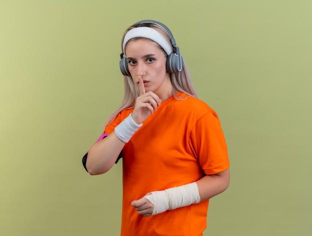 Jovem caucasiana desportiva confiante com suspensórios nos fones de ouvido, pulseiras de tiara e braçadeira de telefone. gestos sinal de silêncio