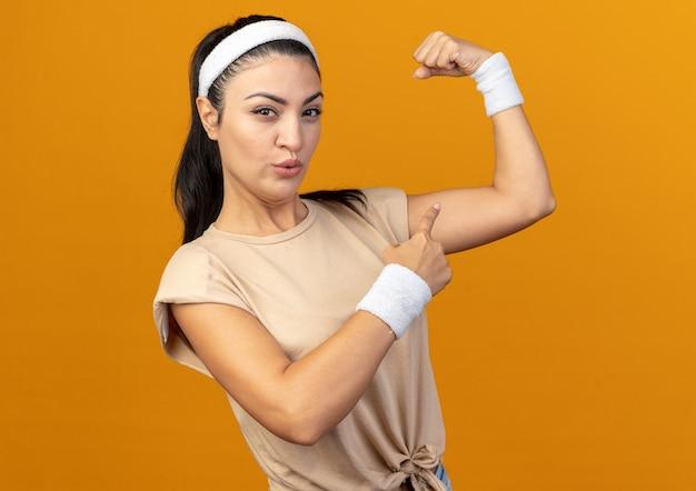 Jovem caucasiana desportiva confiante usando bandana e pulseiras em pé na vista de perfil, olhando para a frente, fazendo um gesto forte apontando para os músculos isolados na parede laranja