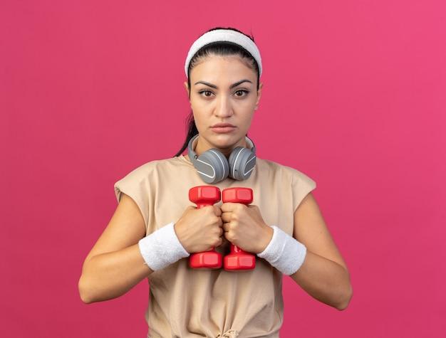 Jovem caucasiana desportiva séria com fita para a cabeça e pulseiras com fones de ouvido ao redor do pescoço, olhando para a frente, segurando halteres isolados na parede rosa