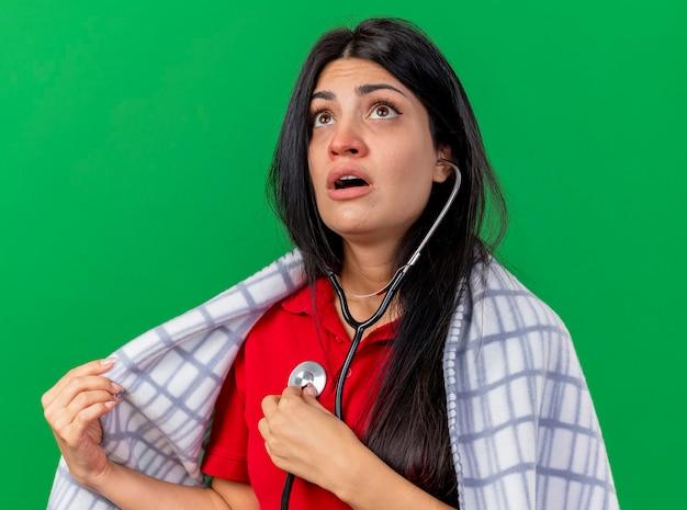 Jovem caucasiana doente concentrada usando um estetoscópio envolto em uma manta, ouvindo os batimentos cardíacos, olhando para cima, agarrando a manta
