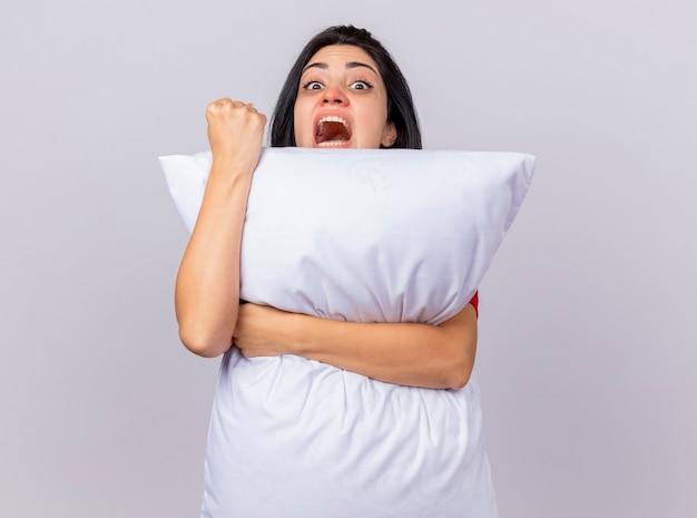 Jovem caucasiana doente confiante abraçando o travesseiro, olhando para a câmera por trás dela, fazendo um gesto forte, isolado no fundo branco com espaço de cópia