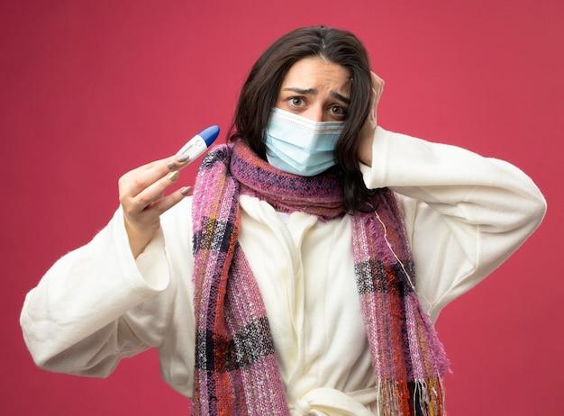 Jovem caucasiana doente e ansiosa usando manto e lenço com máscara segurando o termômetro e mantendo a mão na cabeça isolada na parede carmesim