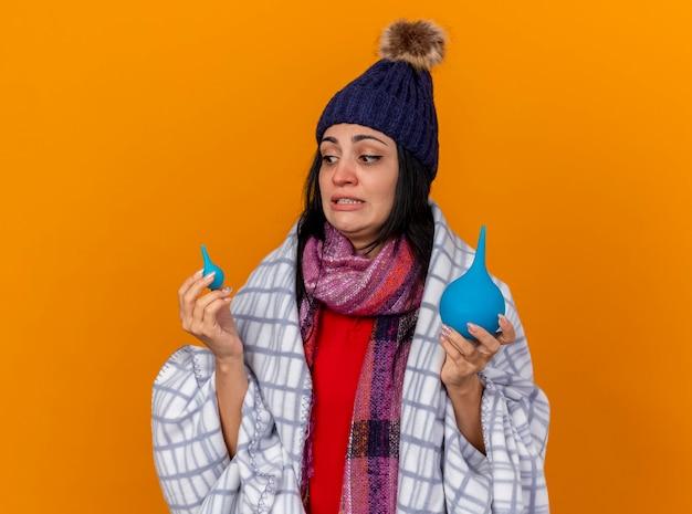 Jovem caucasiana doente impressionada com chapéu de inverno e lenço embrulhado em xadrez segurando enemas olhando para o pequeno isolado em um fundo laranja com espaço de cópia