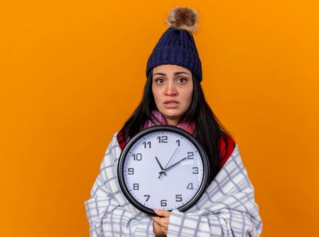 Jovem caucasiana doente impressionada com chapéu de inverno e lenço embrulhado em xadrez segurando um relógio olhando para a câmera isolada em um fundo laranja com espaço de cópia