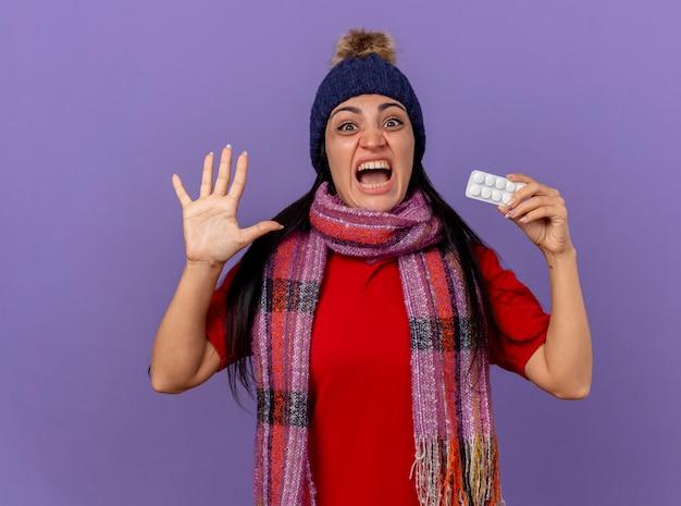 Jovem caucasiana doente, impressionada, usando chapéu e lenço de inverno, mostrando um pacote de comprimidos, olhando para a câmera, mostrando cinco, com a mão isolada no fundo roxo