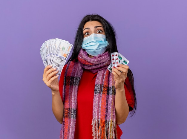 Jovem caucasiana doente, impressionada, usando máscara e lenço segurando dinheiro e pacote de cápsulas, olhando para a câmera, isolada no fundo roxo com espaço de cópia