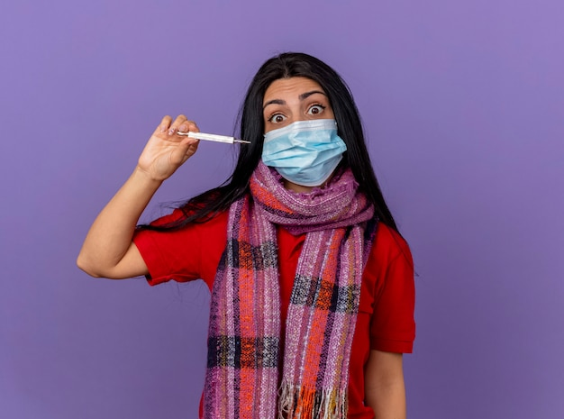 Jovem caucasiana doente, impressionada, usando máscara e lenço segurando um termômetro isolado horizontalmente na parede roxa com espaço de cópia