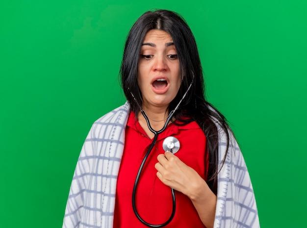 Jovem caucasiana doente, impressionada, usando um estetoscópio envolto em uma manta e ouvindo os batimentos cardíacos, olhando para baixo, isolado em um fundo verde com espaço de cópia