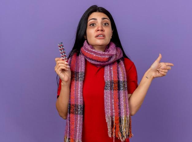 Jovem caucasiana doente, impressionada, usando um lenço segurando um pacote de cápsulas, olhando para a câmera, apontando para o lado isolado no fundo roxo com espaço de cópia
