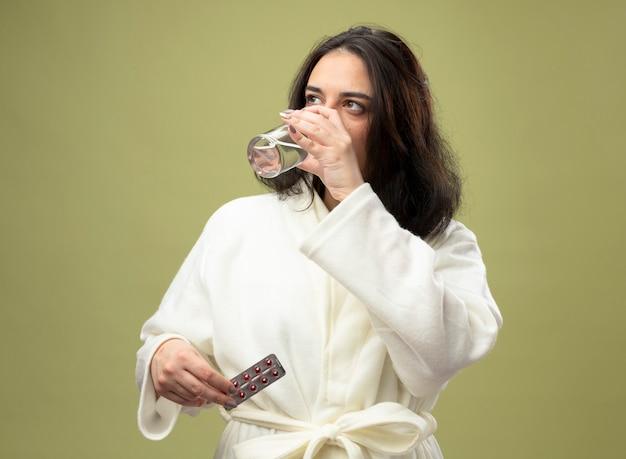 Jovem, caucasiana, doente, vestindo um robe, bebendo um copo de água e segurando um pacote de comprimidos médicos, olhando para o lado isolado no fundo verde oliva