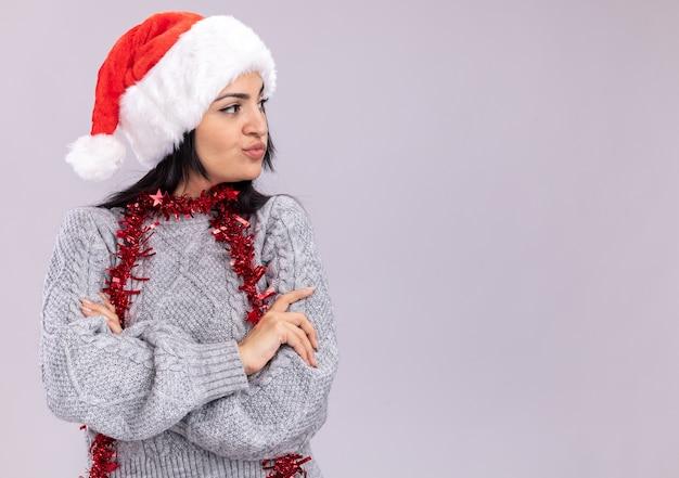 Jovem caucasiana duvidosa usando chapéu de natal e guirlanda de ouropel em volta do pescoço, em pé com a postura fechada, olhando para o lado isolado no fundo branco