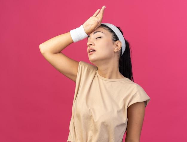 Jovem, caucasiana, esportiva, cansada, usando bandana e pulseiras, segurando a testa com os olhos fechados, isolada na parede rosa