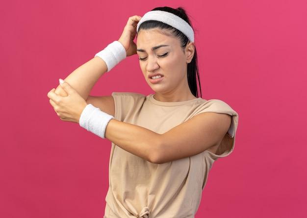 Jovem, caucasiana, esportiva, dolorida, usando bandana e pulseiras tocando a cabeça, colocando a mão no cotovelo, com os olhos fechados, isolada na parede rosa