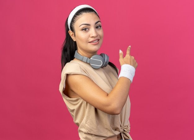 Jovem, caucasiana, esportiva, satisfeita, usando bandana e pulseiras com fones de ouvido ao redor do pescoço, de pé em vista de perfil, olhando para frente, apontando para trás, isolado na parede rosa