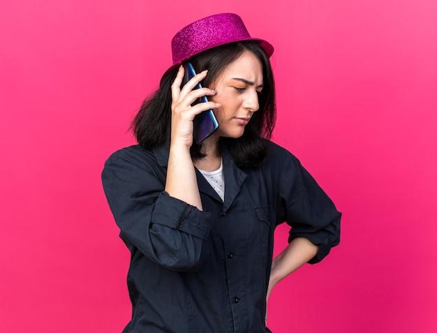 Jovem caucasiana festeira carrancuda usando chapéu de festa, mantendo a mão na cintura, falando ao telefone, olhando para baixo, isolada na parede rosa