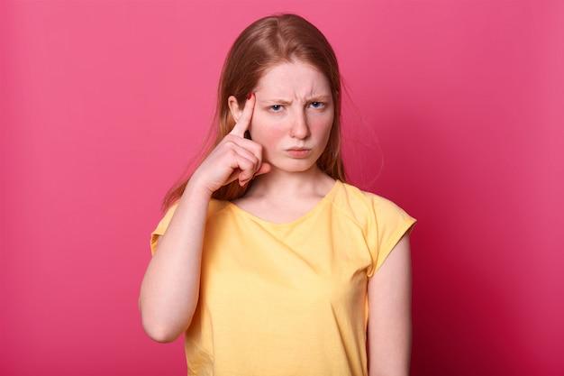 Jovem caucasiana focada tocando templos com os dedos indicadores e franzindo a testa, tem expressão facial pensativa