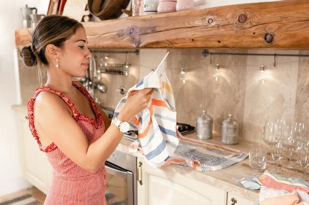 Jovem caucasiana fofa secando pratos com um pano em casa depois de uma festa em uma cozinha rústica