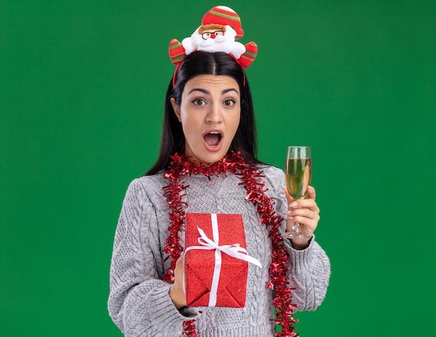 Jovem caucasiana impressionada com bandana de papai noel e guirlanda de ouropel em volta do pescoço, segurando um pacote de presente e uma taça de champanhe, olhando para a câmera isolada sobre fundo verde