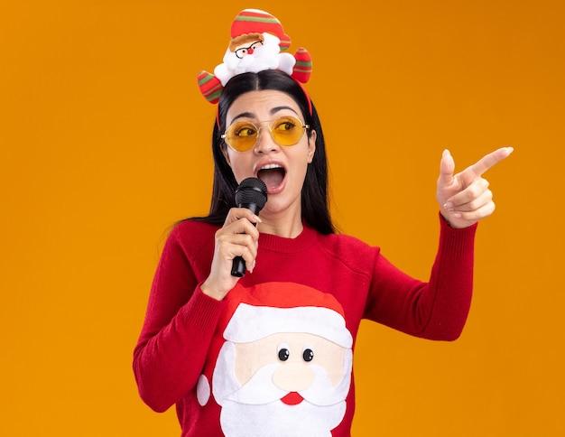 Jovem caucasiana impressionada com bandana de papai noel e suéter com óculos falando no microfone, olhando e apontando para o lado isolado em fundo laranja
