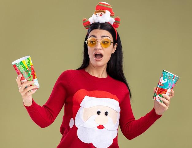 Jovem caucasiana impressionada com bandana de papai noel e suéter com óculos segurando copos de natal de plástico olhando para um deles isolado em fundo verde oliva