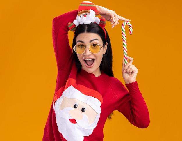 Jovem caucasiana impressionada com bandana de papai noel e suéter com óculos segurando o tradicional bastão de doces de natal perto da cabeça, olhando para a câmera isolada em fundo laranja