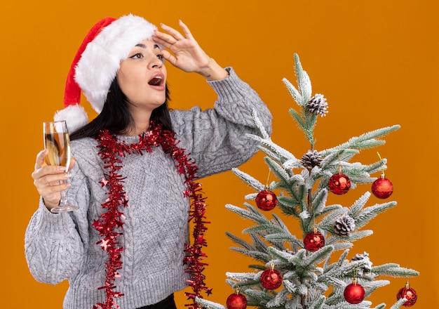 Jovem caucasiana impressionada com chapéu de natal e guirlanda de ouropel em volta do pescoço em pé perto da árvore de natal decorada segurando uma taça de champanhe, olhando para o lado distante, isolada na parede laranja