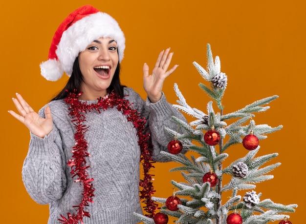 Jovem caucasiana impressionada com chapéu de natal e guirlanda de ouropel no pescoço, em pé perto da árvore de natal decorada, mostrando as mãos vazias isoladas na parede laranja