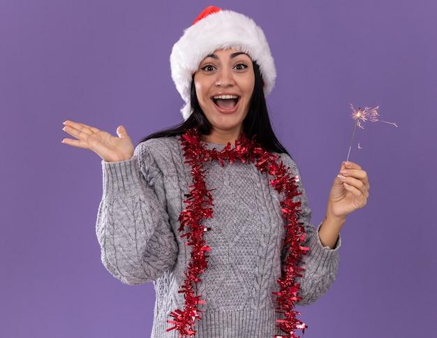 Jovem caucasiana impressionada com chapéu de natal e guirlanda de ouropel pendurada no pescoço segurando um diamante de férias olhando para a câmera, mostrando a mão vazia isolada no fundo roxo