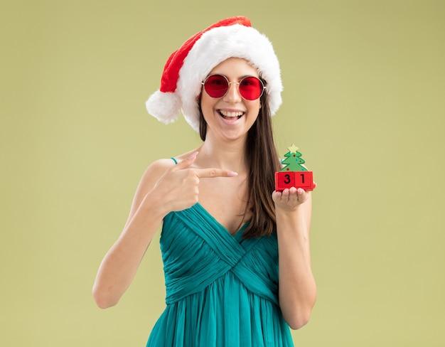 Jovem caucasiana impressionada com óculos de sol e chapéu de papai noel segurando e apontando para o enfeite de árvore de natal