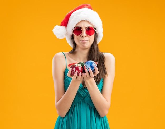 Jovem caucasiana impressionada com óculos de sol e chapéu de papai noel segurando enfeites de bola de vidro