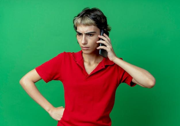 Jovem caucasiana insatisfeita com corte de cabelo de duende falando no telefone, olhando para baixo, colocando a mão na cintura isolada sobre fundo verde