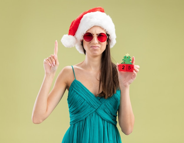 Jovem caucasiana insatisfeita com óculos de sol e chapéu de papai noel segurando um enfeite de árvore de natal e apontando para cima