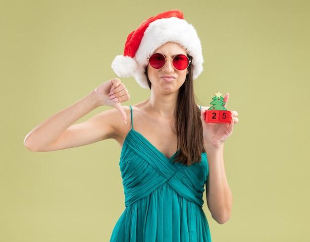 Jovem caucasiana insatisfeita com óculos de sol e chapéu de papai noel segurando um enfeite de árvore de natal e polegar para baixo