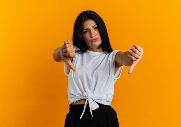 Jovem caucasiana irritada com um polegar para baixo com as duas mãos