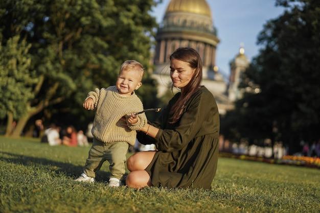 Jovem caucasiana, mãe do filho pequeno sentado na grama em frente à catedral de st isaacs e ajudando o menino a segurá-lo com a mão. imagem com foco seletivo. foto de alta qualidade