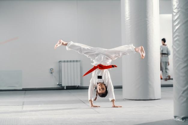Jovem caucasiana no dobok, fazendo carrinho de mão com as pernas abertas na aula de taekwondo.