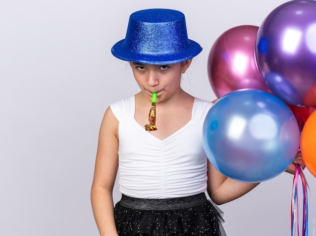 Jovem caucasiana ofendida com chapéu de festa azul segurando balões de hélio e soprando apito de festa isolado na parede branca com espaço de cópia