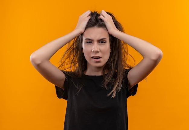 Jovem caucasiana preocupada com uma camiseta preta agarrada pelo cabelo em uma parede laranja isolada