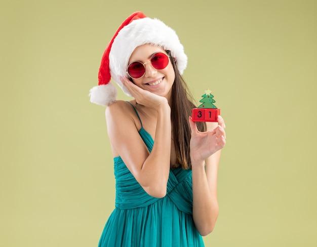 Jovem caucasiana satisfeita com óculos de sol e chapéu de papai noel coloca a mão no rosto e segura o enfeite de árvore de natal