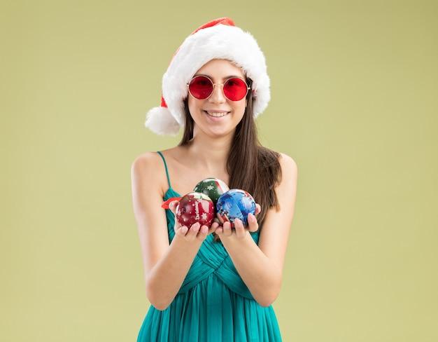 Jovem caucasiana satisfeita com óculos de sol e chapéu de papai noel segurando enfeites de bola de vidro