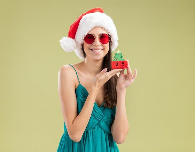 Jovem caucasiana satisfeita com óculos de sol e chapéu de papai noel segurando um enfeite de árvore de natal