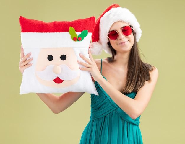 Jovem caucasiana satisfeita com óculos de sol e chapéu de papai noel segurando um travesseiro de papai noel