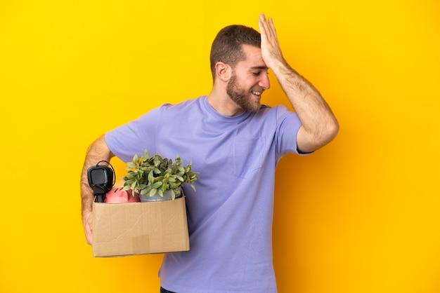 Jovem caucasiana se mexendo enquanto apanha uma caixa cheia de coisas isoladas em um fundo amarelo percebeu algo e pretende a solução