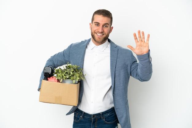 Jovem caucasiana se mexendo enquanto pega uma caixa cheia de coisas isoladas em branco saudando com a mão com expressão feliz